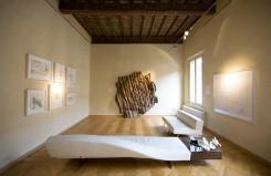 Maria Livia Brunelly, galleria d'arte in casa (Ferrara) – una stanza della casa con una chaise longue in primo piano, un'opera a forma di rosa in tessuto, quadri appesi alla parete di sinistra; il soffitto a cassettoni lignei.