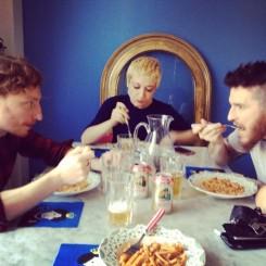 tre persone (una donna e due uomini) al tavolo mentre mangiano