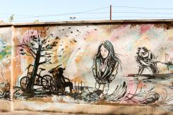soggetto del murale è una ragazza inginocchiata vicino a un albero, due bici e altri soggetti più piccoli secondari