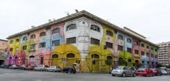 soggetto del murale che copre le diverse facciate contigue dell'edificio sono strani volti pelosi e di diversi colori incastrati uno accanto all'altro