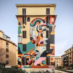 mural colorato sull'intera facciata della palazzina che rappresenta attraverso grandi macchie di colore un volto circondato da natura morta