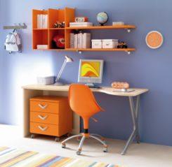 un angolo studio per bambini: scrivania legno chiaro, sedia, cassetti e mensole arancioni