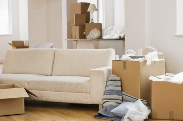 trasloco intelligente un divano e un soggiorno pieno di scatoloni e carta da imballaggio